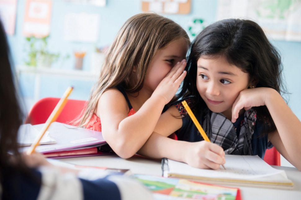 Mädchen Im Unterricht flüstern sich etwas zu